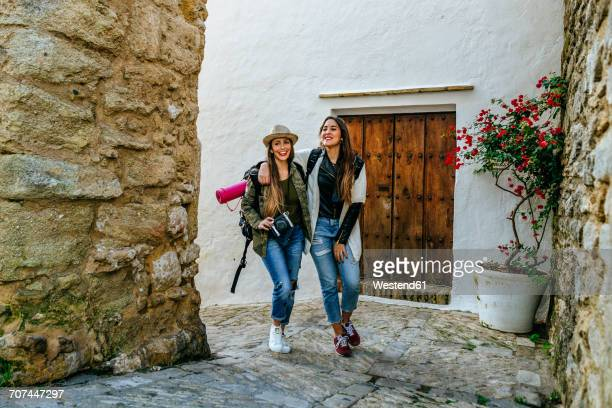 Two smiling young women on a trip walking in a town