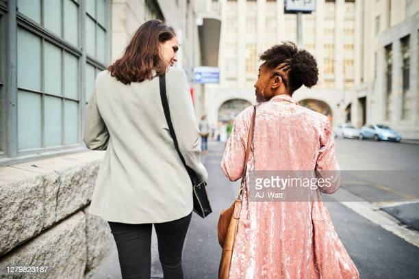 twee glimlachende jonge vrouwen die samen spreken terwijl het lopen in de stad - zij aan zij stockfoto's en -beelden