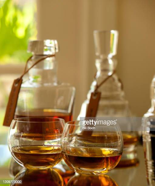 two snifters of brandy or whiskey and crystal decanters behind them in a elegant home bar or drink establishment—part of a series - bourbon whisky foto e immagini stock