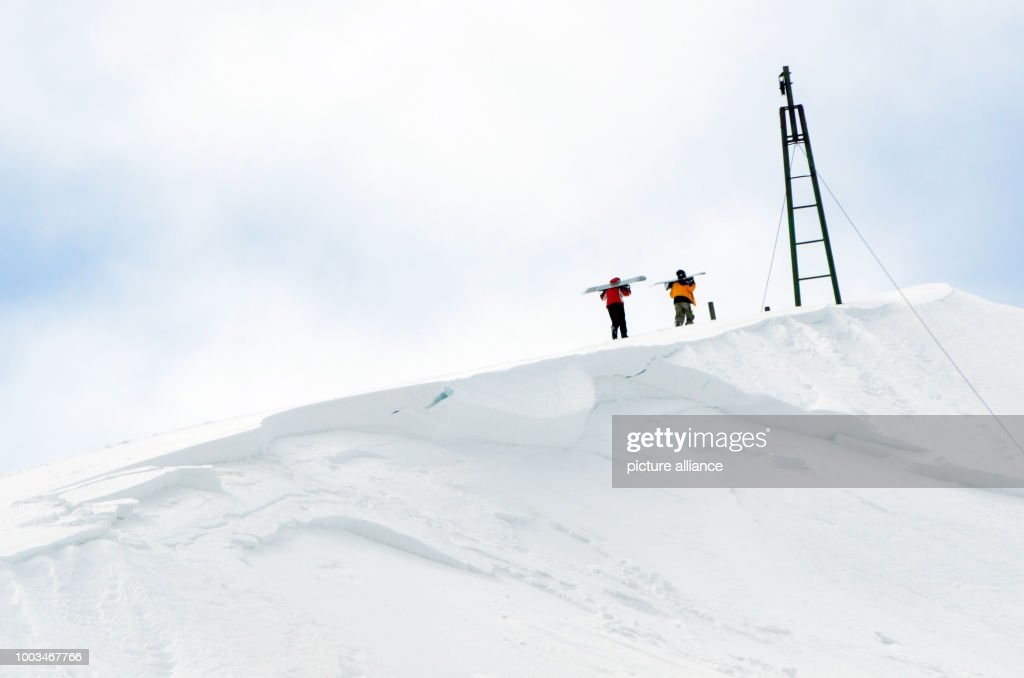 5196ec65d64d Two snowboarders carry their boards up the mountain after strong ...