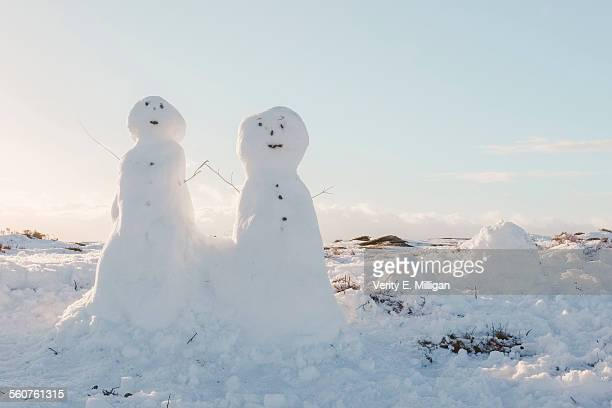 Two snowmen holding hands