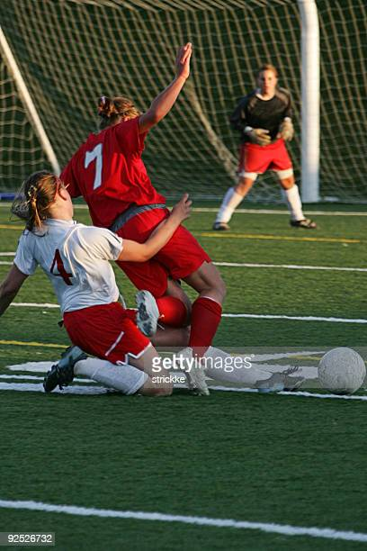 Two Soccer Midfielders Fight For Ball as Goalie Waits Anxiously