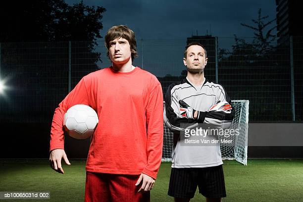 Two soccer player on football pitch, looking away