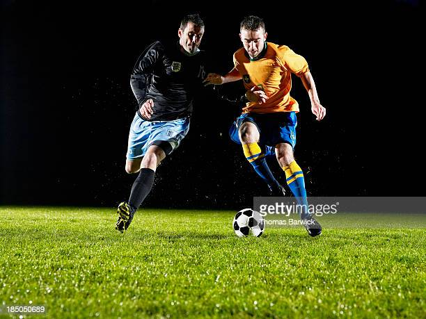 Two soccer players challenging for ball