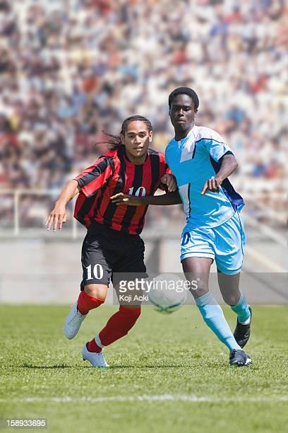 two soccer players challenging for the ball - atacante de futebol imagens e fotografias de stock