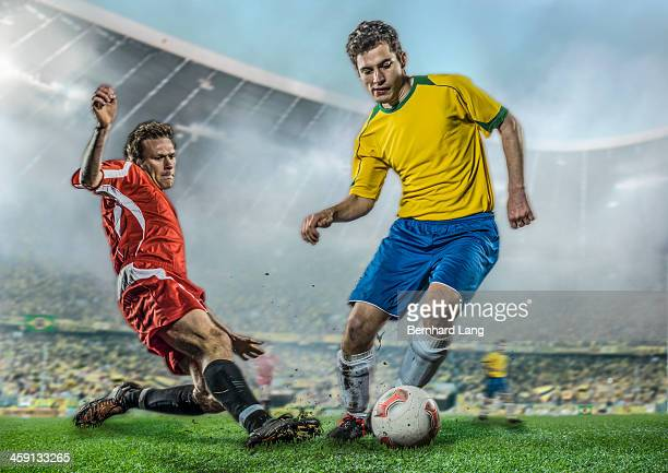 two soccer players fighting for ball in stadium - tackling stock pictures, royalty-free photos & images