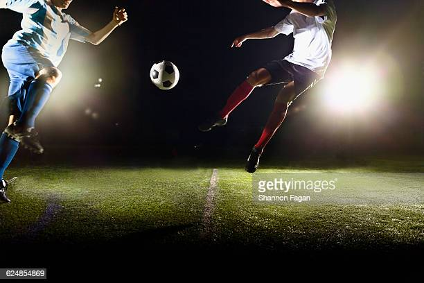 Two soccer players fighting for the ball