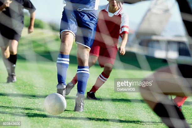 Two Soccer Players from Opposing Teams Chasing Ball