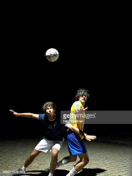 Two soccer players heading ball, night