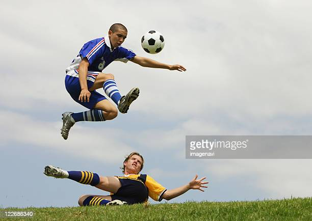 two soccer players in sliding tackle - slide tackle stock pictures, royalty-free photos & images