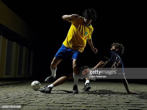 Two soccer players kicking ball on street, night