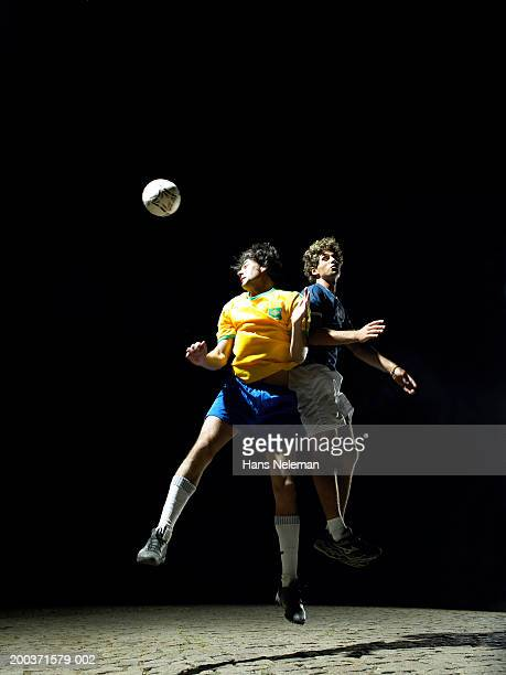 Two soccer players leaping in mid air, heading ball, night