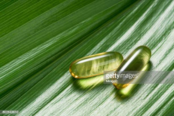 Two Soft Capsules on Green Leaf