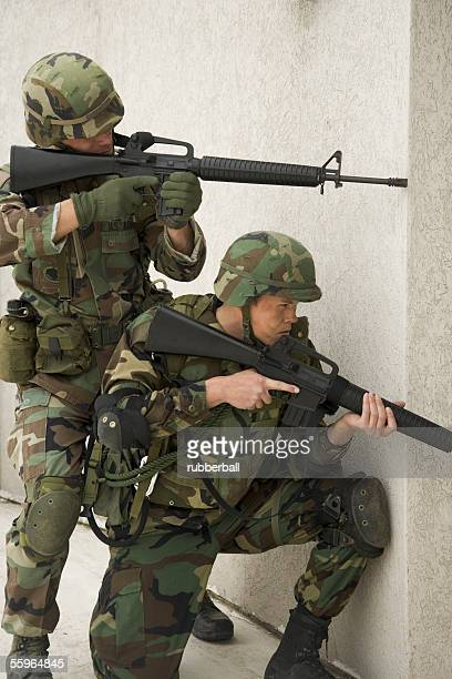 two soldiers aiming their rifles - boots rifle helmet stock pictures, royalty-free photos & images