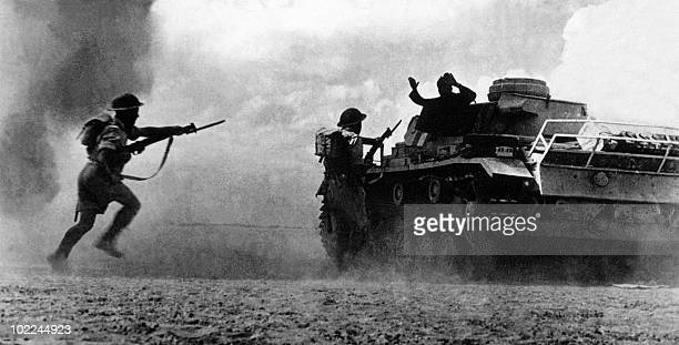 Two soldiers belonging to the Commonwealth and Allied forces aim at a German soldier surrendering atop his tank 25 October 1942 as a sandstorm clouds...