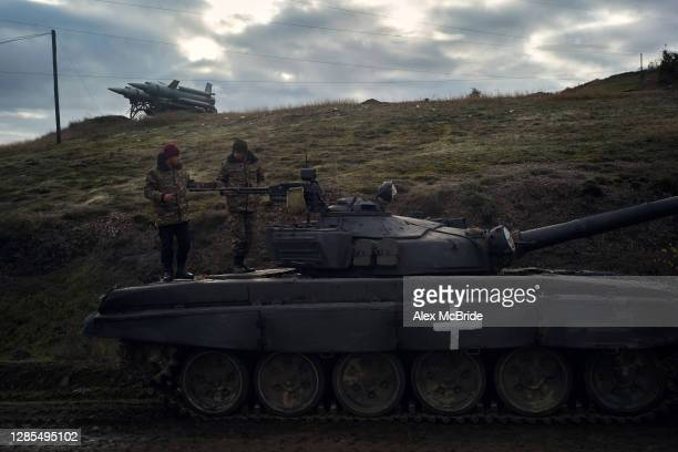 Two soldiers chat on top of a tank by the side of the road where the final days of battle had occurred between Armenian forces and approaching Azeri...