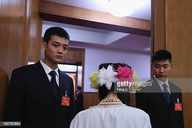 Two soldiers dressed as ushers check the pass of an ethnic minority delegate at the enterance of the meeting room for the fifth plenary meeting of...