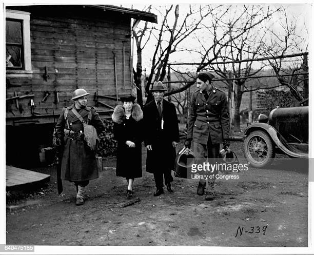 Two soldiers escort an elderly Japanese American couple during their evacuation from Bainbridge Island to a relocation center 1942