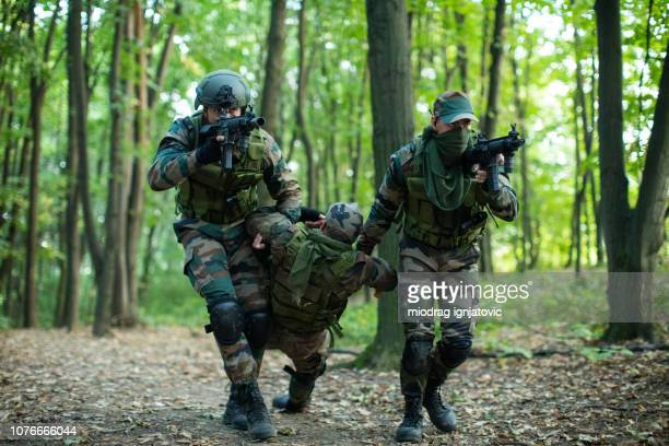 two soldiers helping their injured friend - army training stock pictures, royalty-free photos & images
