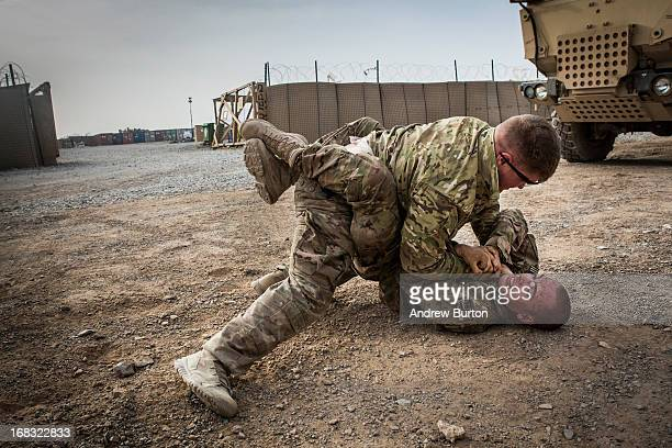 Two soldiers in the US Army's 1st Battalion 36th Infantry Regiment Charlie Company wrestle during a maintenance stop at Forward Operating Base...