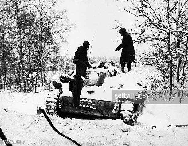 Two soldiers look at a dead crewman on a snowcovered German tank during the Battle of the Bulge St Vith Belgium | Location St Vith Belgium