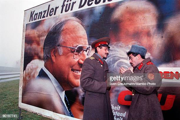 Two soldiers of the Soviet Union talk in front of an election campaign poster showing Germany´s Chancellor Helmut Kohl on December 2 in Schwerin...