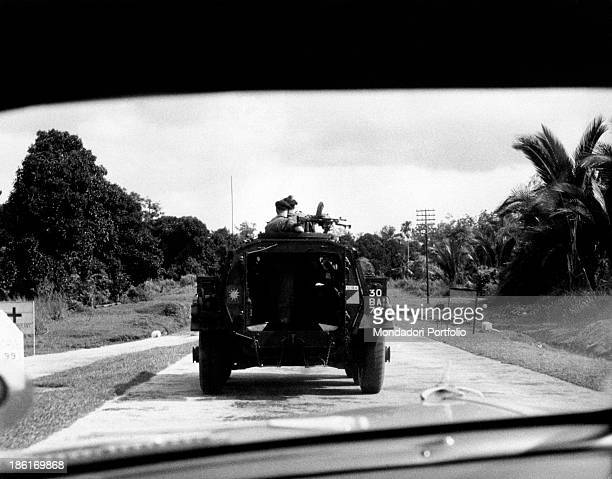 Two soldiers on the turret of a light armoured car going along a road Malaysia 1950s