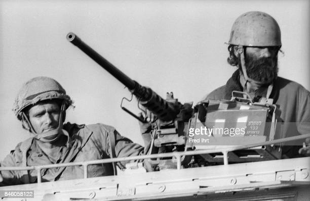 Two soldiers on top of their armored vehicle one armed with amachine gun on the Golan Heights during the Yom Kippur war