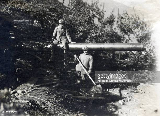 Two soldiers pose with a Marina cannon 152 near the 'Passo Buole' photograph Italy Cima Mezzana July 1918 The weapon was hidden from aircraft...