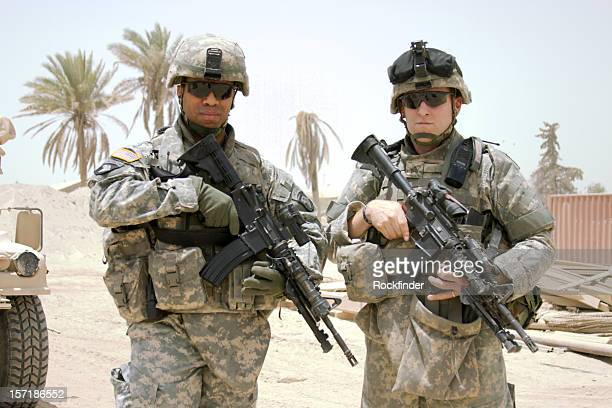 two soldiers posing on camera in the middle east - army soldier stock photos and pictures