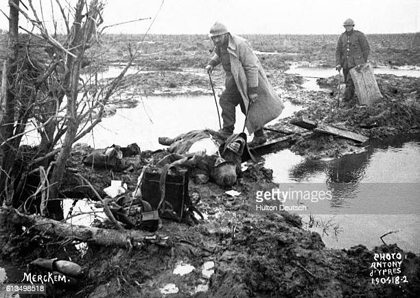 Two soldiers search the muddy battlefields of Ypres for lost or abandoned war materials or other valuables In the first Battle of Ypres October 1914...