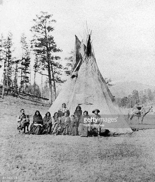 Two soldiers sit on either side of a group of captured Sious Indians following the Battle of Slim Buttes Wyoming September 1876 The group sits in...