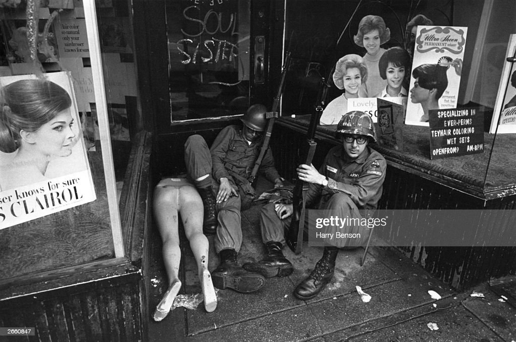 Two soldiers sitting in a shop doorway, amid the broken dummies, during riots in Newark, New Jersey, July 1967.