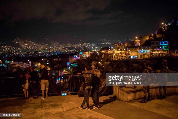 Two soldiers stand guard as people enjoy the night on the Day of the Little Candles in Medellin Colombia on December 7 2018 The Day of the Little...