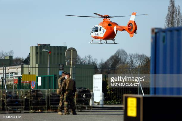 Two soldiers wearing a face masks stand past a medical helicopter taking off from the military field hospital outside the Emile Muller Hospital in...