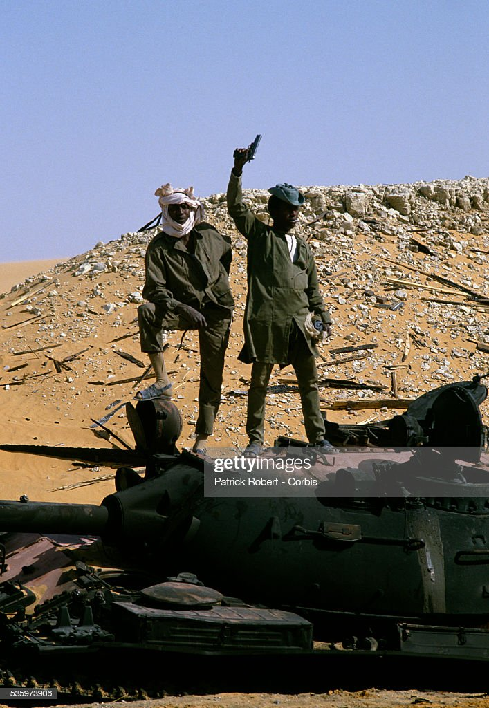 Two soldiers with the Forces Armees Nationales Chadiennes (FANT), or National Army of Chad, stand atop a captured Libyan military tank in Faya-Largeau. The FANT mission in early 1987 was to reconquer the Borkou-Ennedi-Tibesti Prefecture and recover the territory in northern Chad that had been under Libyan control. For the first time in four years, refugees who fled the Libyan invasion returned to the country.