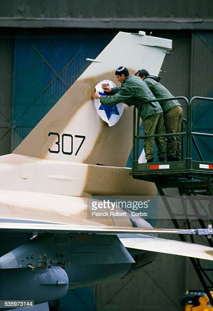 Two soldiers with the Israeli armed forces decorate an F16C Fighting Falcon with the Israeli flag American armed forces sent into the port of Haifa...