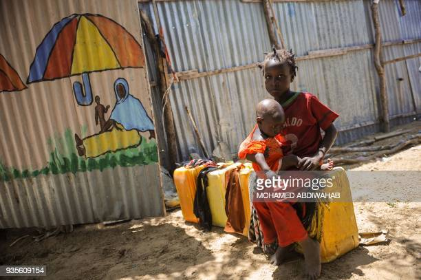 TOPSHOT Two Somali girls sit on empty jerrycans as they wait to collect water at the Tawakal IDP camp on the outskirts of Mogadishu Somalia on March...