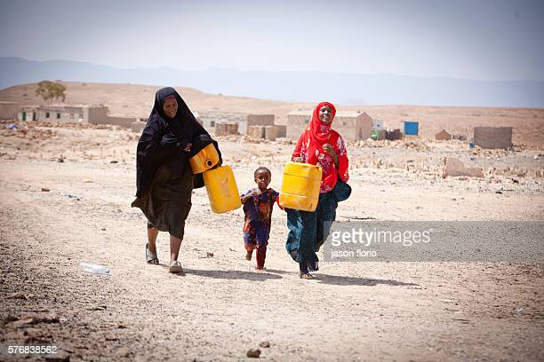Two Somali ladies and a child carrying water containers to a distribution point operated by Puntland Maritime Police Force The Puntland Maritime...