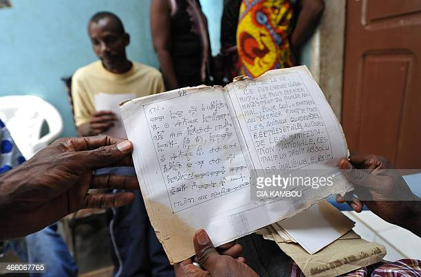 Two sons of late Ivorian artist Frederic Bruly Bouabre show a manuscript with pictograms by their father at the family home in Abidjan on January 30...