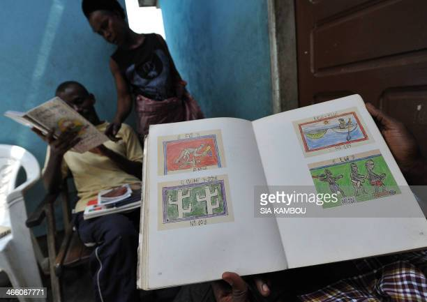 Two sons of late Ivorian artist Frederic Bruly Bouabre show a manuscript with drawings by their father at the family home in Abidjan on January 30...