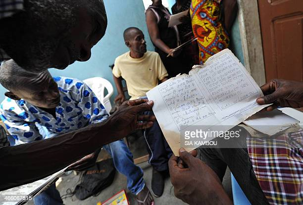 Two sons of late Ivorian artist Frederic Bruly Bouabre show a manuscript with pictorgrams by their father at the family home in Abidjan on January 30...