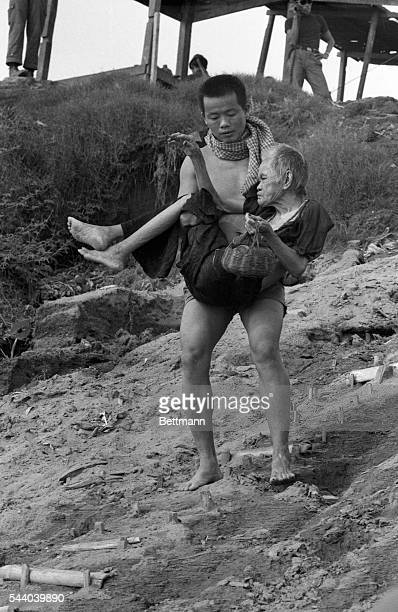 Two South Vietnamese soldiers help two old Cambodian natives flee from the fighting area One carries an old man and the other a floor mat while he...