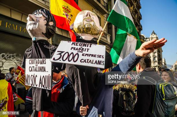 Two Spanish loyalist protesters carry posters and puppets representing two leaders of the catalan independence movement the Puigdemont President and...