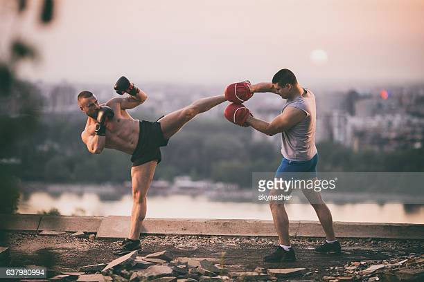 Two sparring partners exercising kick boxing at sunset.