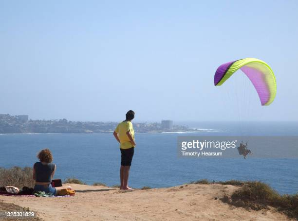 two spectators (man and woman) look out at a paraglider; ocean, coastline and blue sky beyond - timothy hearsum fotografías e imágenes de stock