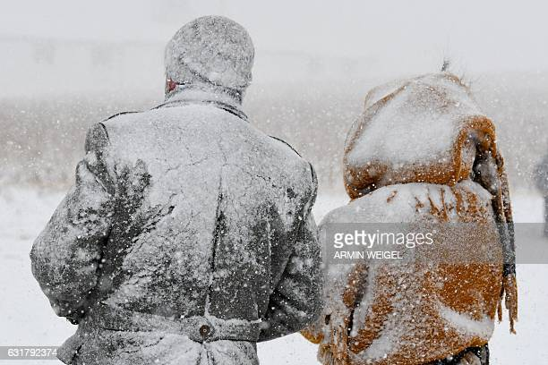 Two spectators of a horse-drawn sleigh race are covered in snow as they watch the event on January 15, 2017 in Rinchnach, southern Germany. / AFP /...