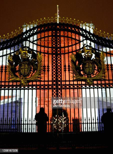 Two spectators stand outside the gates of Buckingham Palace 31 December 2003 which is illuminated with the British Flag by a projection that is part...