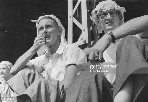 Two spectators wearing knotted handkerchiefs against the heat as they watch preOlympic trials at White City Stadium London July 1948