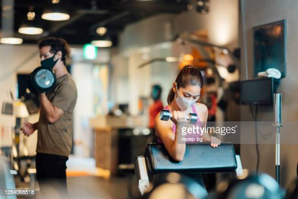 two sports persons wearing protective face masks and training in gym while keeping social distancing - gym stock pictures, royalty-free photos & images